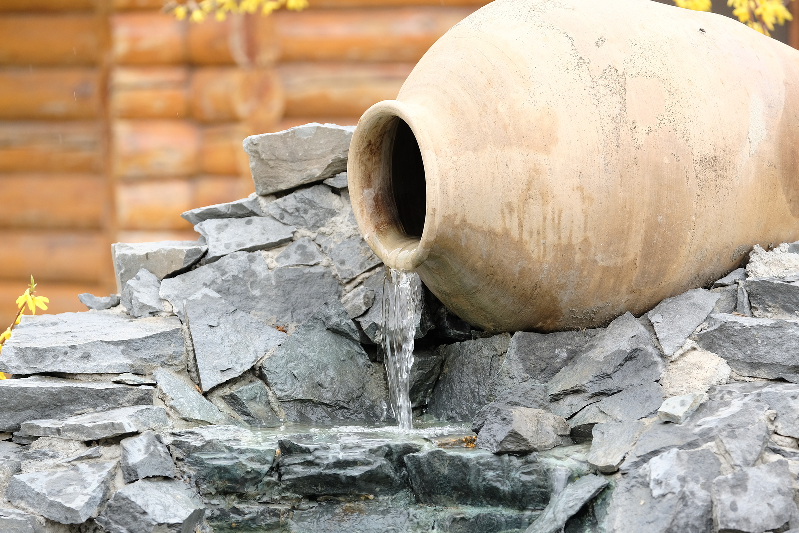 Decorative garden waterfall made with stone jar